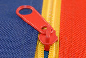 Red zipper on blue and yellow canvas — Stock Photo