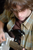 Fourteen year old boy playing electric guitar — Stock Photo
