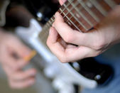 Hands on frets of guitar with shallow depth of field — Stock Photo