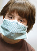 Twelve year old boy with surgical mask on — Stock Photo