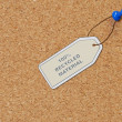 Recycled material tag attached to corkboard with thumb tac - Stock Photo