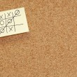 Game of tic tac toe on note on corkboard - Stock Photo