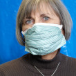 Attractive senior woman wearing protective medical mask - Stock Photo