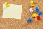 Cork board with note and thumb tacks — Stock Photo