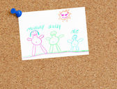 Cork board with childs family drawing tacked up — Stock Photo