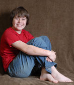 Attractive pre teen boy sitting down and happy — Stock Photo
