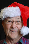 Happy smiling senior man in santa hat — Stock Photo
