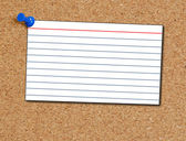 Index card thumb tacked to corkboard background — Stock Photo
