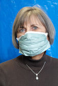 Attractive senior woman wearing protective medical mask — Stock Photo