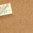Game of tic tac toe on note on corkboard — Stock Photo