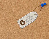 Recycled material tag attached to corkboard with thumb tack — Stock Photo