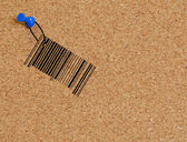 Barcode dangling from string fastened to corkboard — Stock Photo