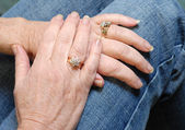Diamond rings on married seniors hands — Stock Photo