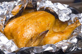 Juicy golden chicken in foil — Stock Photo