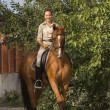 Beautiful smiling women riding a brown horse in countryside — Stock Photo