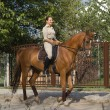 Beautiful smiling women riding a brown horse in countryside. — Stock Photo #15405963