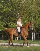 Young woman with dog riding a horse through woodland — Stock Photo