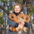 Smiling blonde woman middle aged with her dogs and enjoying outd — Stock Photo #17190627