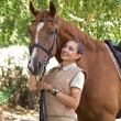 Portrait of a beautiful horsewoman standing with horse outdoors - Stock Photo