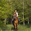 Beautiful smiling girl riding a brown horse through woodland — Stok fotoğraf