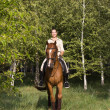 Beautiful smiling girl riding a brown horse through woodland — Stock Photo