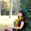 Female sitting under a tree - Stockfoto
