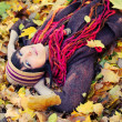 Girl lying in leaves. - Stockfoto