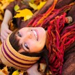 Girl portrait lying in leaves. - Stockfoto
