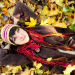 Girl in autumn leaves. - Stockfoto