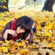 Girl lying in leaves. - ストック写真