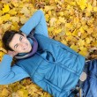 Young man sitting in park. - Stock Photo
