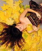 Girl lying in leaves. — Stock Photo