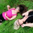 Girls laying in grass — Stock fotografie