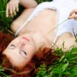 Girl portrait, lying in grass field. — Stock Photo #14203247