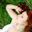 Girl portrait, lying in grass field. — Stock Photo