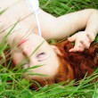 Female lying on grass field — Stock Photo