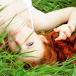 Female lying on grass field — Stock Photo #14203286