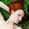 Girl portrait, lying in grass field. — Stock Photo #14203318