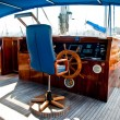 Cockpit inside a boat with a wood wheel. - Stock Photo