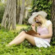 Girl with book outdoor. - Stock Photo