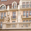 Building in historical style with statue in the foreground — Foto de Stock