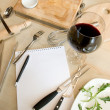 Utensils, notebook and glass of wine — Stock Photo #14209636