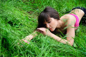 Girl portrait, lying in grass field. — Stock fotografie