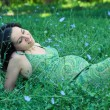 Pregnant woman relaxing on grass. - Foto Stock