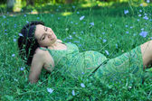 Pregnant woman relaxing on grass. — Stock Photo