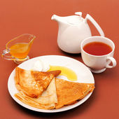 Pancakes with honey and tea. — Stock Photo