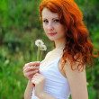 Young redhead female with dandelions. -  