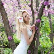 Young woman in white dress in spring park — Stock Photo
