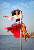 Pole dance girl in dress and hat. — Stock Photo