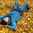 Young man laying in foliage. — Stock Photo